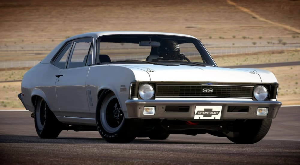 A white 1970 Chevy Nova is on a racetrack.