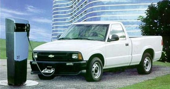 A white Chevy s10 plugged into a charging station