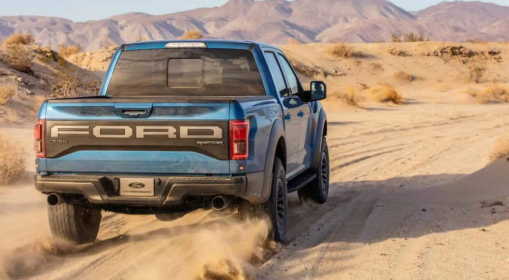 A blue 2019 Ford Raptor from behind, available at Ford dealers, is driving away in the desert.