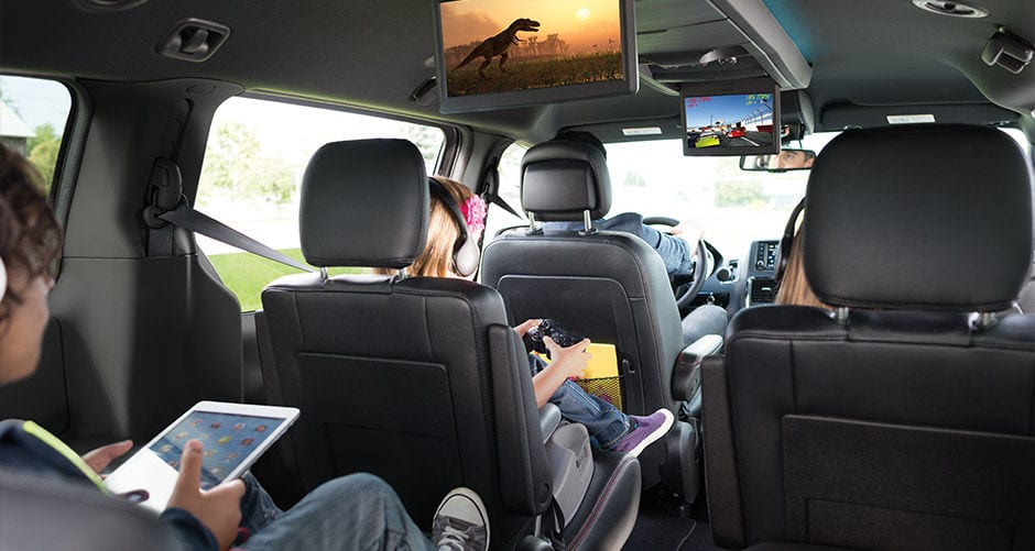 Kids in the back of a 2016 Dodge Grand Caravan are using the built in monitors.