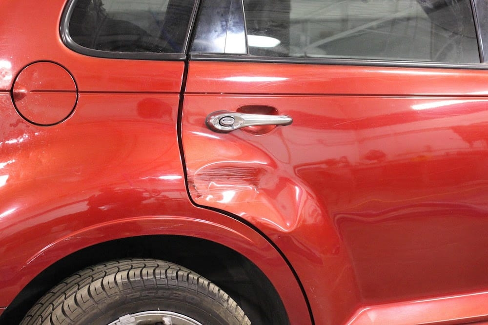 Dented Rear Quarter Panel On Red Jeep Cherokee