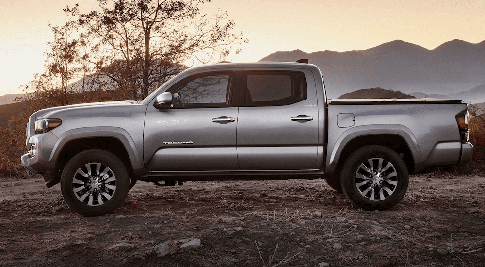 A future silver 2020 Toyota Tacoma is shown at sunset with mountains in the distance.