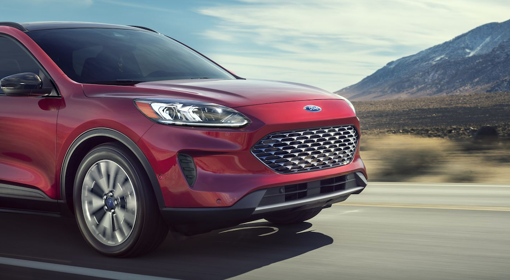 A red 2020 Ford Escape Hybrid is driving with mountains in the distance.