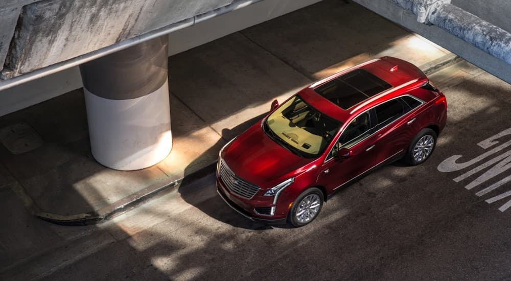 A red 2017 Cadillac XT5 is shown from above under an overpass.