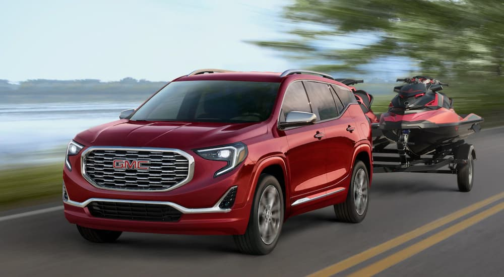 A red 2019 GMC Terrain Denali is towing red jet skis. Comparing towing and performance when looking at the 2019 GMC Terrain vs 2019 Jeep Cherokee.