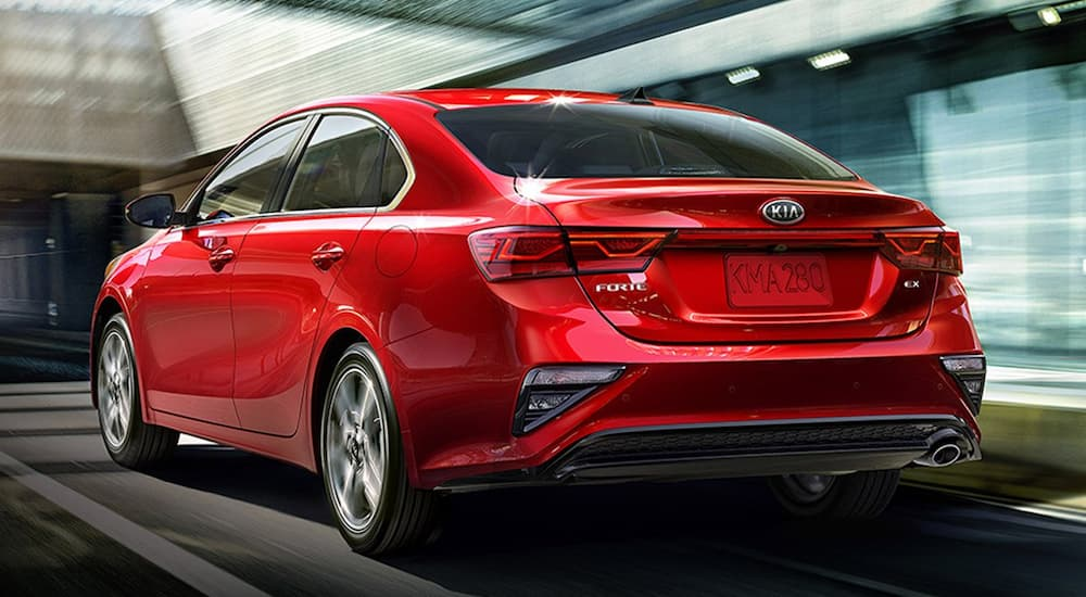 A red 2019 Kia Forte is past blurry buildings in Allentown, PA.