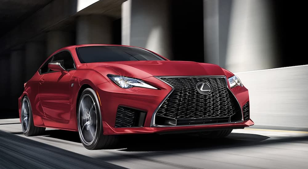 A red 2020 Lexus RCF, with its new release in current auto news, is driving in front of buildings.