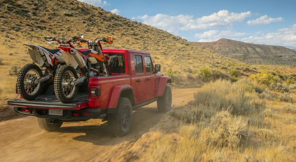 A red 2020 Jeep Gladiator is driving on a dusty trail with dirt bikes in the bed.