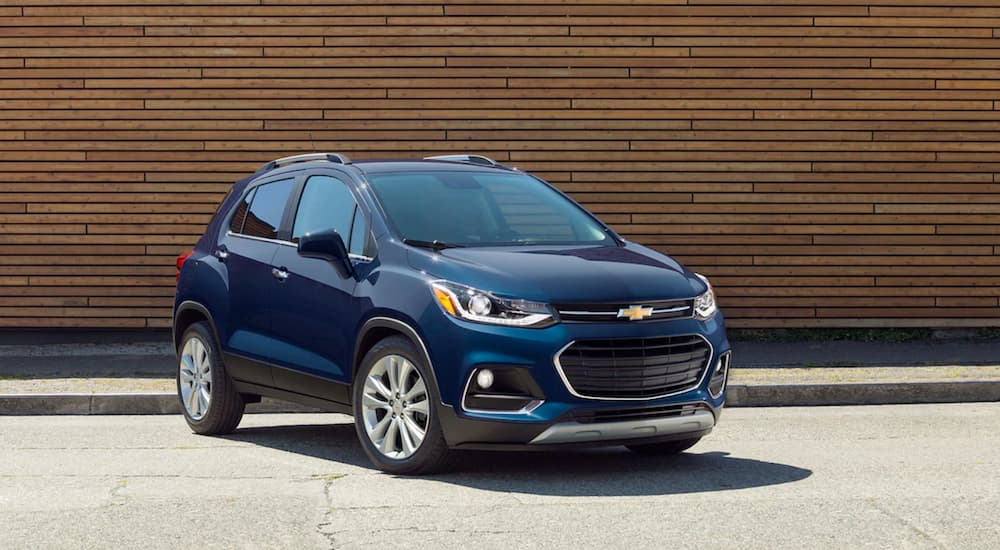 A blue 2019 Chevy Trax is parked in front of a wood wall.