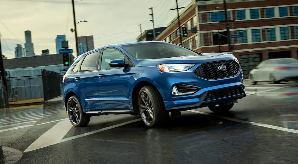 A blue 2019 Ford Edge ST, which wins when comparing the 2019 Ford Edge vs 2019 Kia Sorento, is taking a corner in an intersection.
