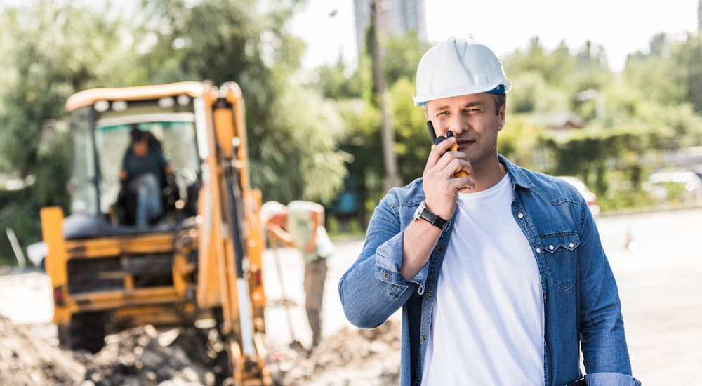 A construction worker is talking on a walkie-talkie in an area where many commercial vehicles will be passing.