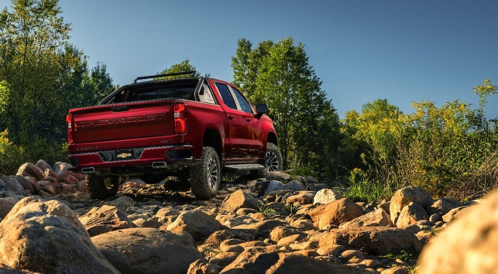 The red 2018 SEMA Chevy Silverado RST OffRoad Concept is on rough off road terrain.