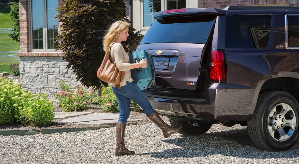 A woman is loading a suitcase into the back of her 2016 Chevrolet Tahoe Z71.