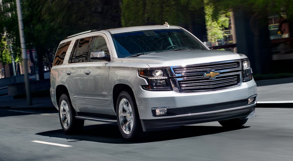 A silver 2019 Chevy Tahoe is driving on a multi-lane city road.