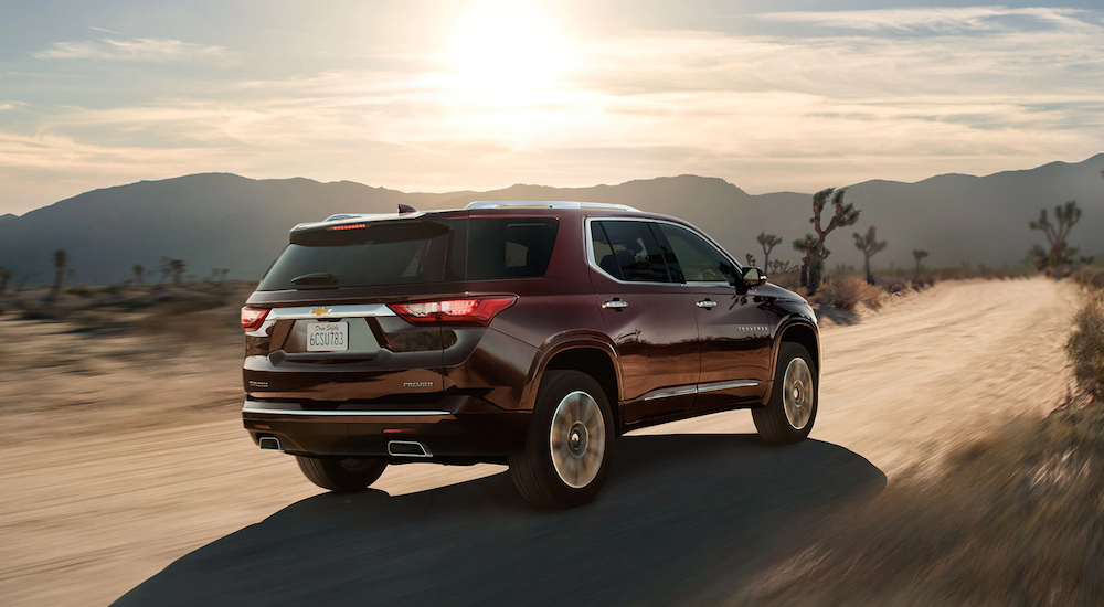 A burgundy 2019 Chevy Traverse is driving through the desert.