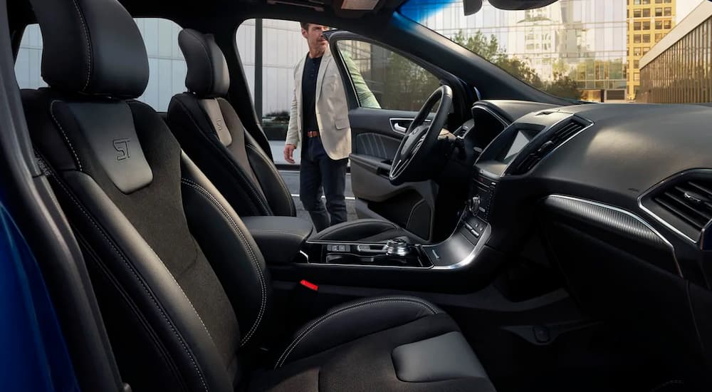 A man is getting into his 2019 Ford Edge with black interior.