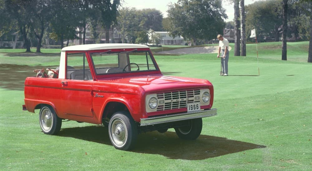 A red 1966 Ford Bronco is on a golf course.