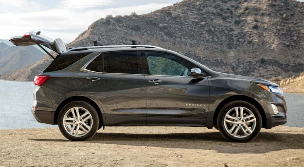A grey 2020 Chevy Equinox is parked at a lake with the trunk open.