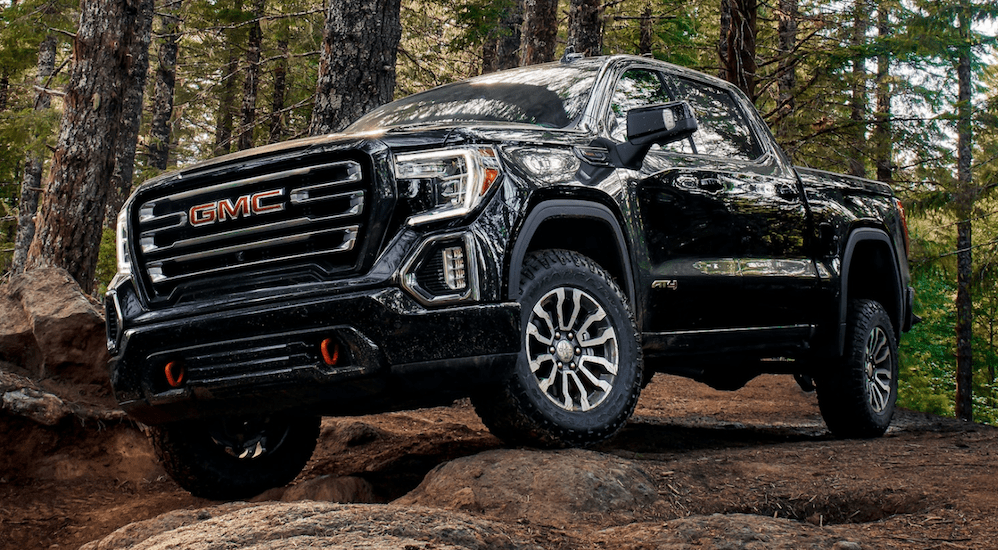 A black 2020 GMC Sierra 1500 AT4 is driving over a rock pile in the woods.