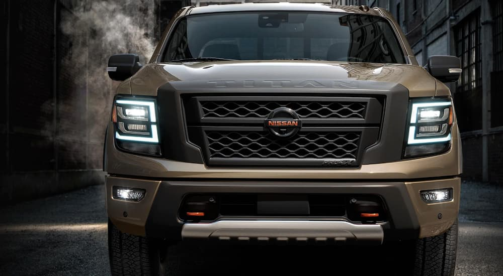 A tan 2020 Nissan Titan is parked in a dark alley with the head lights on.