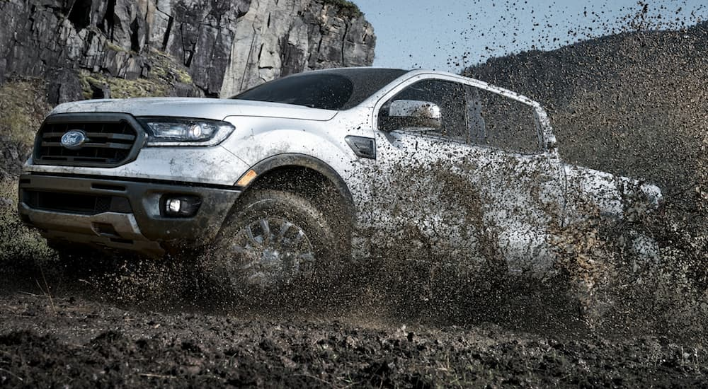 Mud is spraying into the air while a silver 2020 Ford Ranger drives through a mud pit.