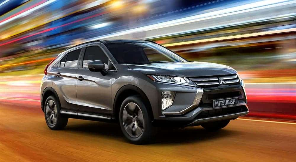 A grey 2020 Mitsubishi Eclipse Cross is driving past blurred city lights at night after leaving a Mitsubishi dealer.