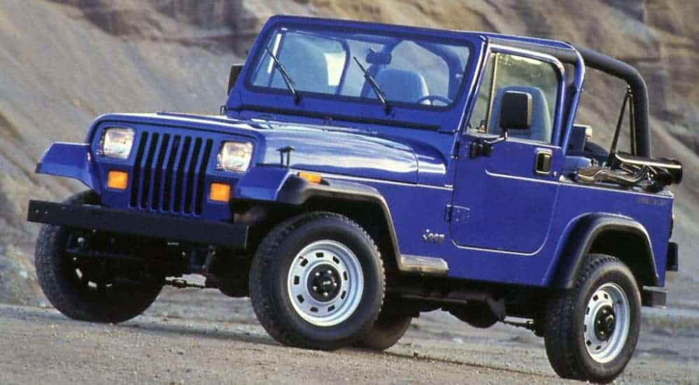 A blue 1990 Jeep YJ is parked on a dirt trail.
