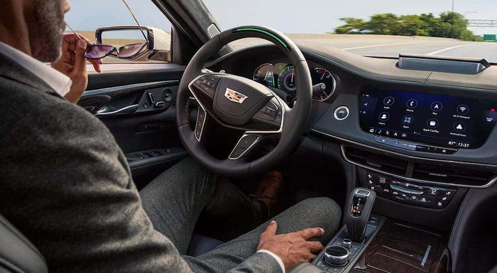 A man is sitting in the front seat on the black leather interior of a 2020 Cadillac CT6.