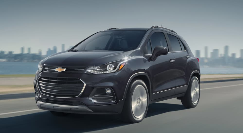 A black 2020 Chevy Trax is driving on a highway with a city skyline in the distance.