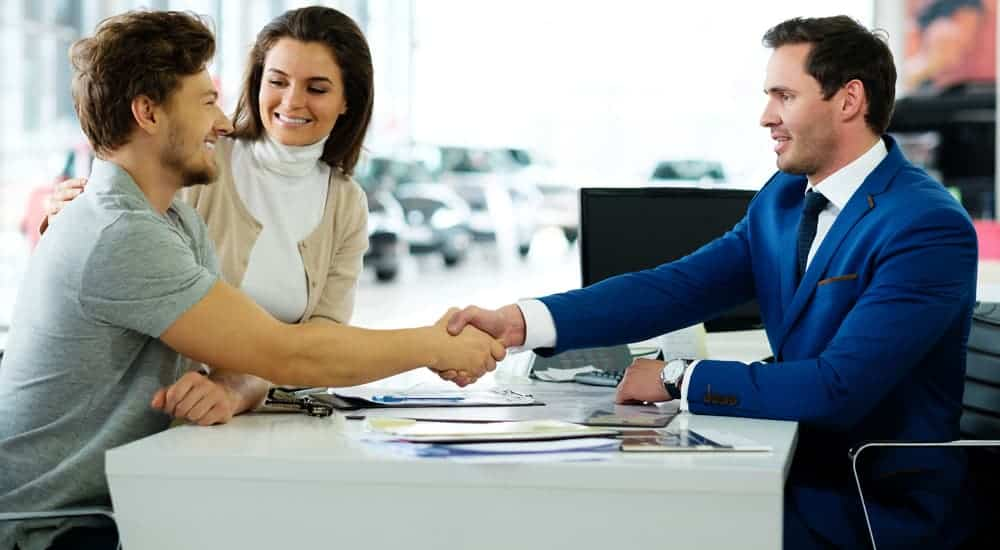 A smiling customer is shaking the hand of a car salesman.