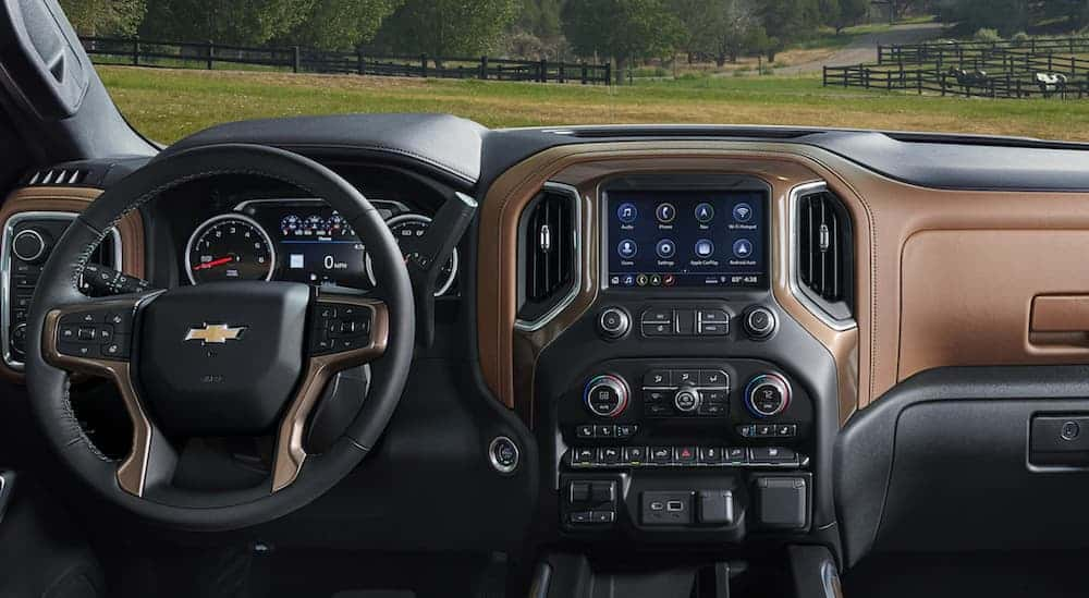 The front black and brown leather interior of a 2020 Silverado 1500 is shown with an infotainment system.