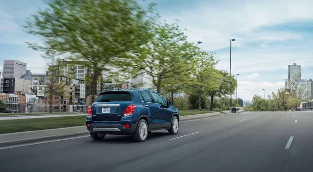 A blue 2020 Chevy Trax is driving towards a city.