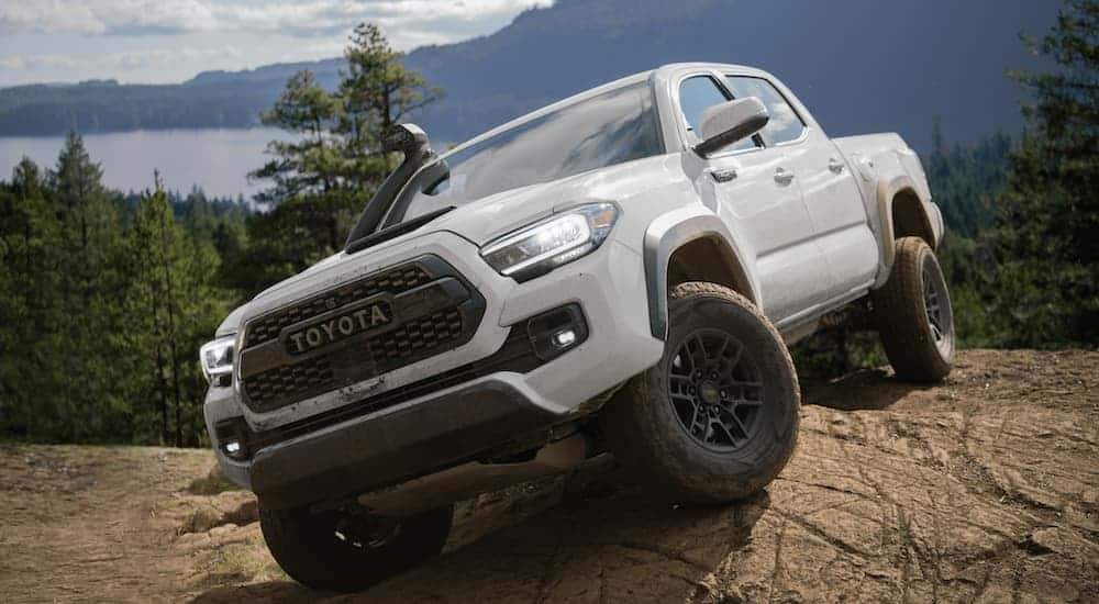 A white 2020 Toyota Tacoma is parked on a rock in front of a mountain and lake.