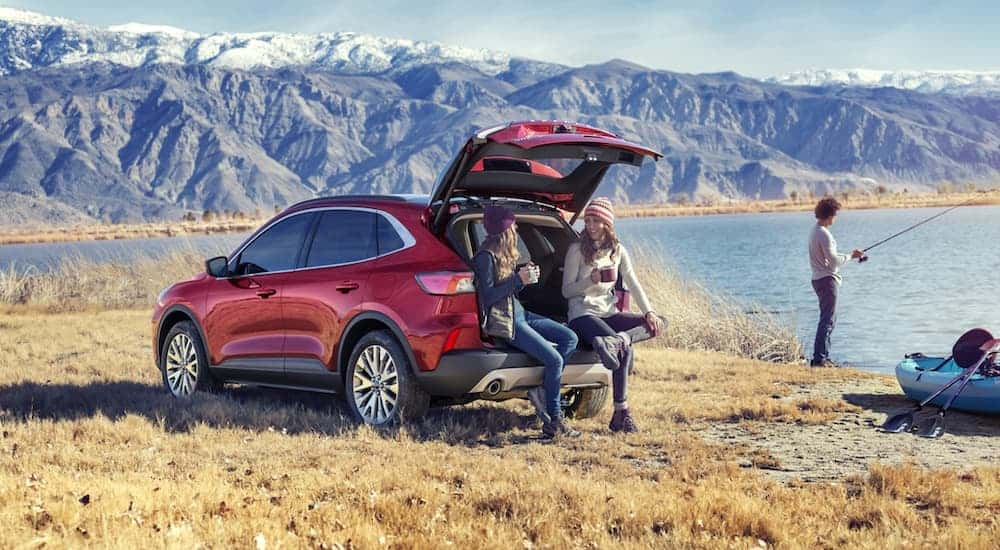 Two gils are sitting in the back of a 2020 Ford Escape while a man fishes at a mountain lake.