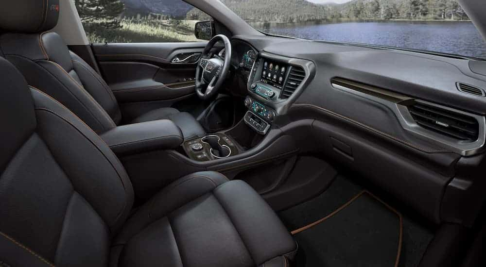 The front black leather interior of a 2020 GMC Acadia AT4 is shown with an infotainment system.