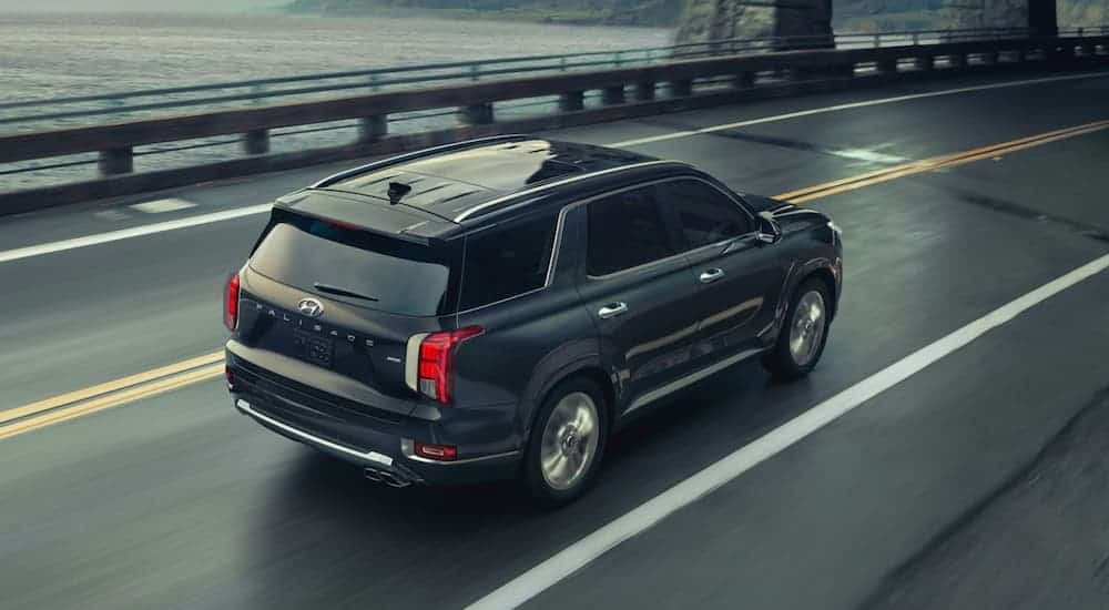 A dark grey 2020 Hyundai Palisade is driving on a highway next to the ocean.