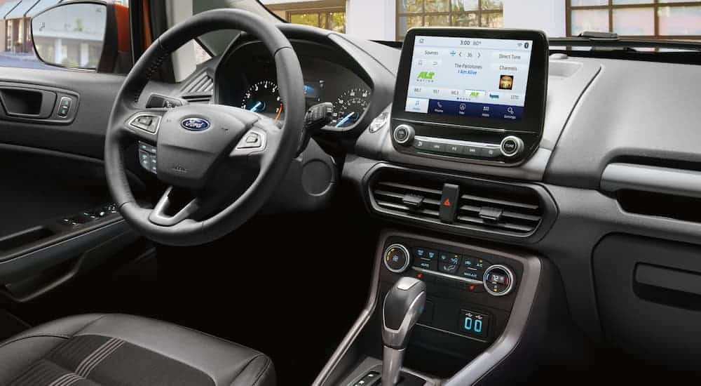 The front black leather interior of a 2020 Ford Ecosport is shown with an infotainment system.