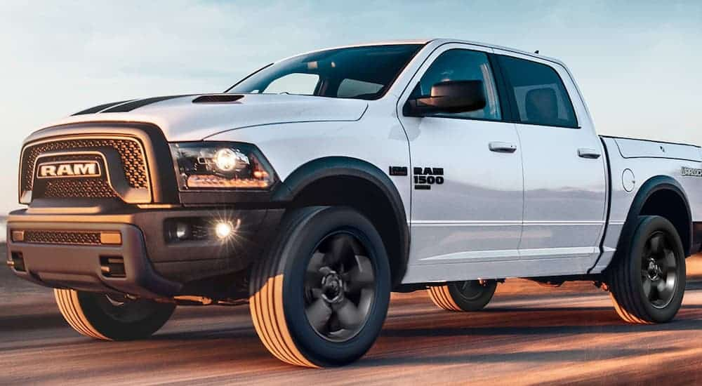 A white 2020 Ram 1500 Classic is driving on the highway.