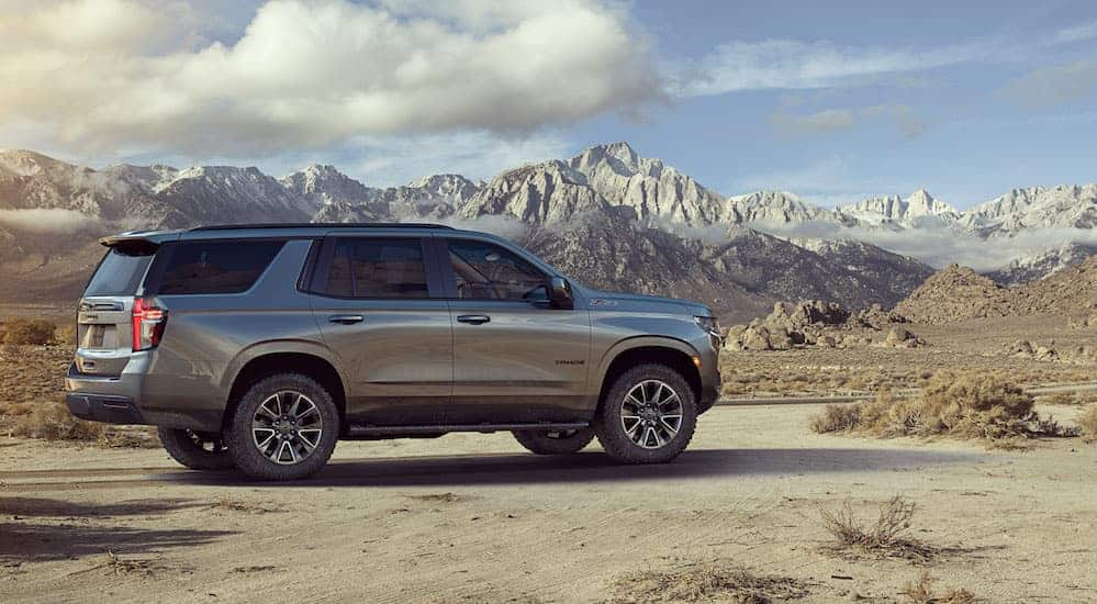 A grey 2021 Chevy Tahoe Z71 is parked on a dirt trail with snow covered mountains in the distance.