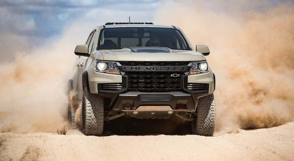 A tan 2021 Chevy Colorado ZR2 is driving on a dirt road and kicking up sand.