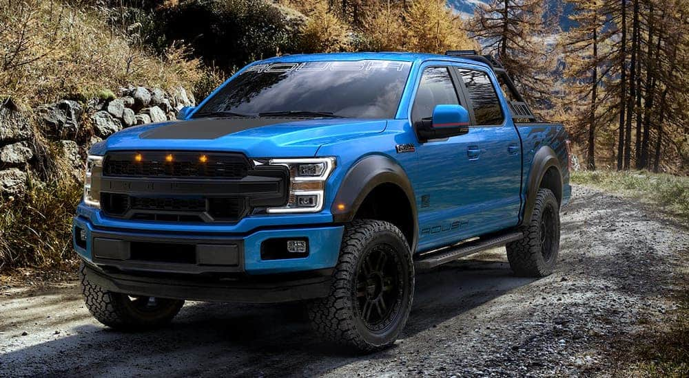 One of the popular Ford Trucks, a blue 2020 Ford F-150 Roush SC is driving on a dirt trail.