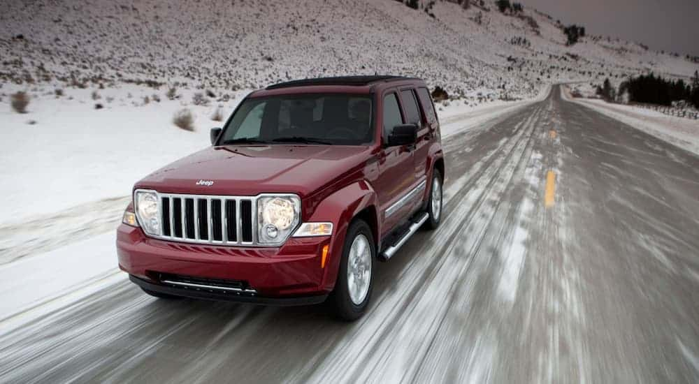 A red 2011 Jeep Patriot is driving on a snowy road after leaving a used car dealership.