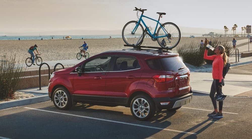 A red 2020 Ford EcoSport is parked at a beach with a bike on the roof.