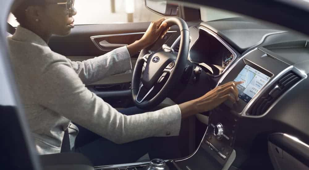 A woman is using the touch screen in a 2020 Ford Edge.