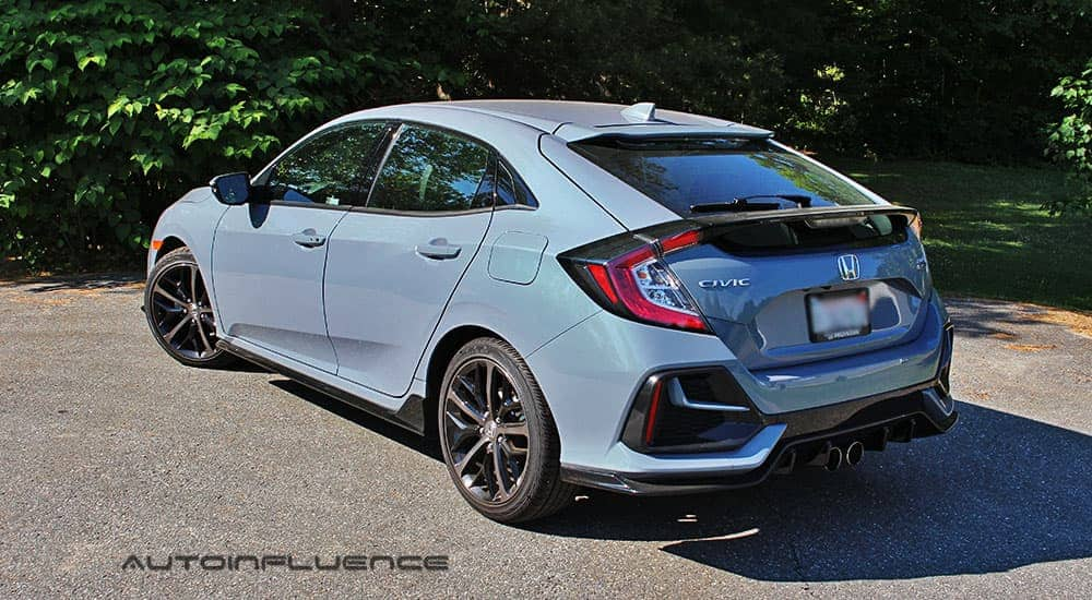 A blue 2020 Honda Civic Hatchback is shown from the rear in front of trees.