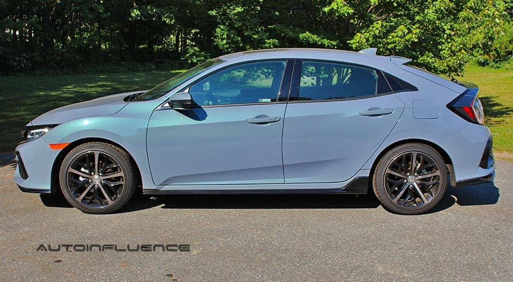 A blue 2020 Honda Civic Hatchback is sown from the side in front of trees.