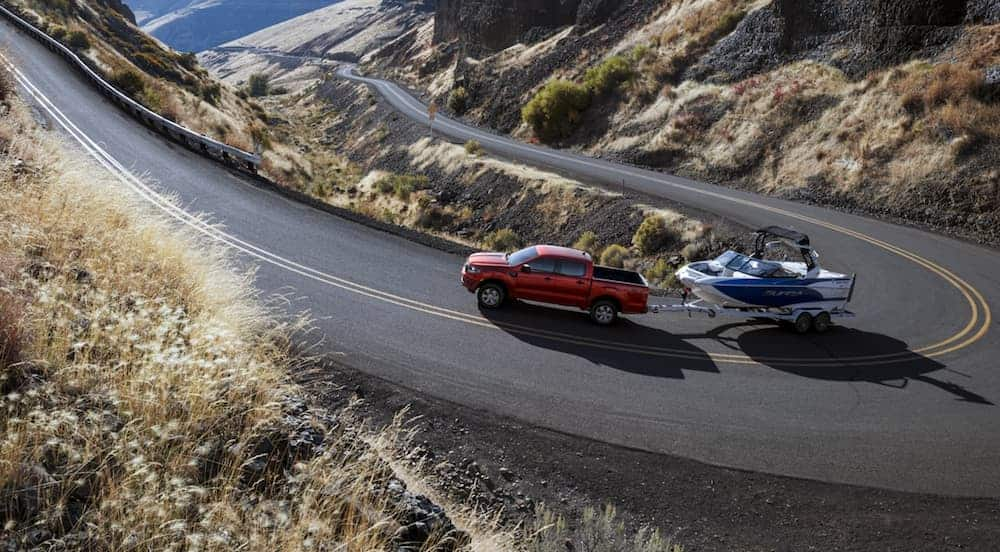 A red 2020 Ford Ranger is towing a boat on a winding mountain road.