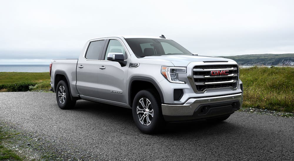 A silver 2020 GMC Sierra 1500 is parked in front of a body of water.