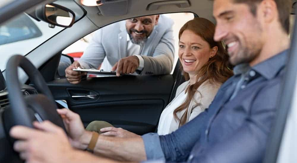 A salesman is talking to a couple in a car at a local used car dealership.