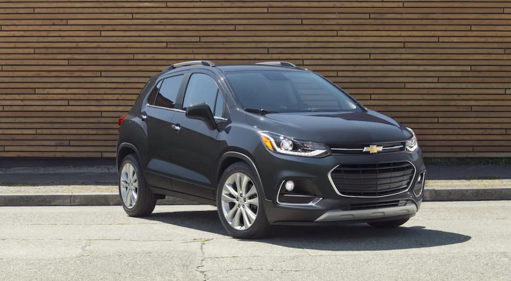 A black 2020 Chevy Trax is parked in front of a wooden wall.